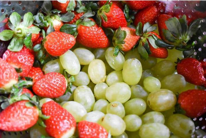 washed green grapes and strawberries in colander