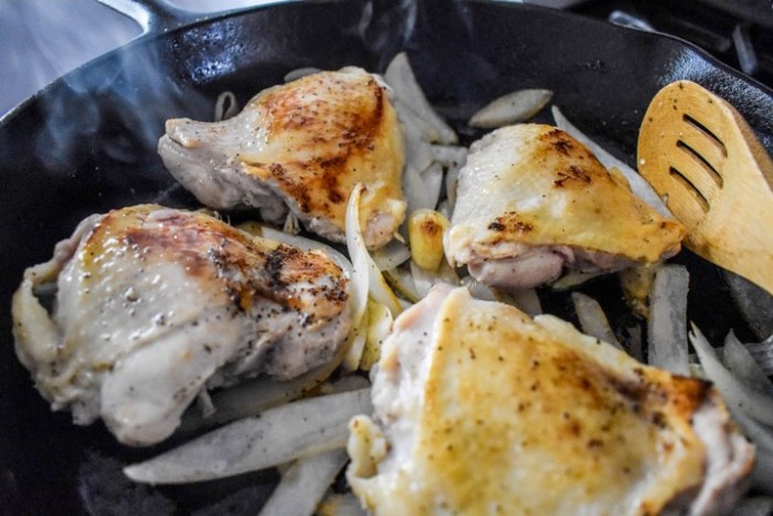chicken thighs cooking in a cast iron skillet with onion and garlic.