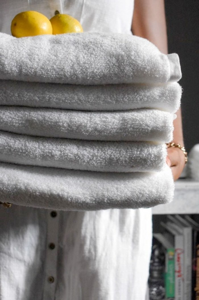 holding stack of fresh white towels and lemons