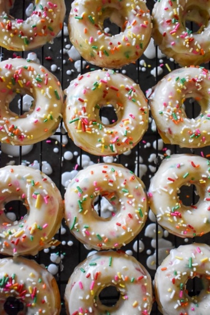 Make these easy and amazing funfetti birthday cake donuts for any day of the year! They're baked with sprinkles, double-dipped in glaze then topped with MORE sprinkles. by Dash of Jaz