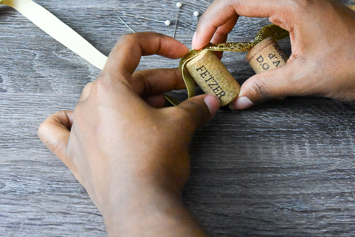 holding wine cork against gold ribbon