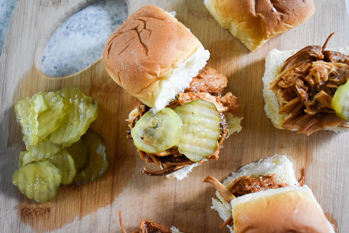 overhead view of slow cooker pulled bbq chicken sliders on a cutting board