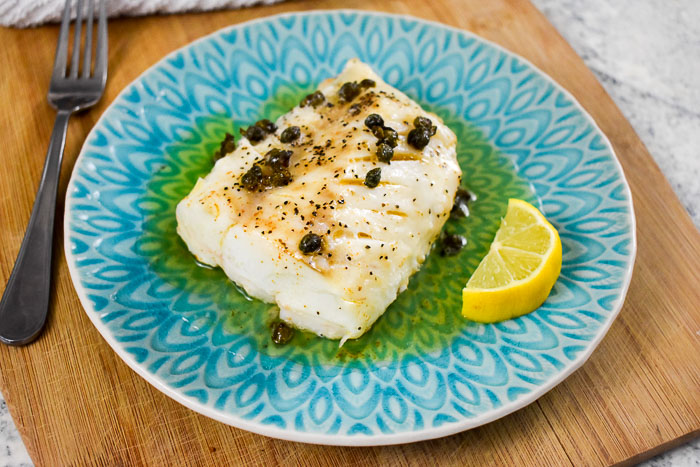 cooked cod filet topped with capers and brown butter with a lemon wedge on the side