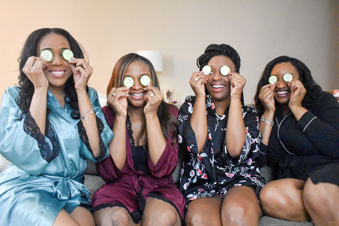 women placing cucumber slices on eyes for at-home spa treatment