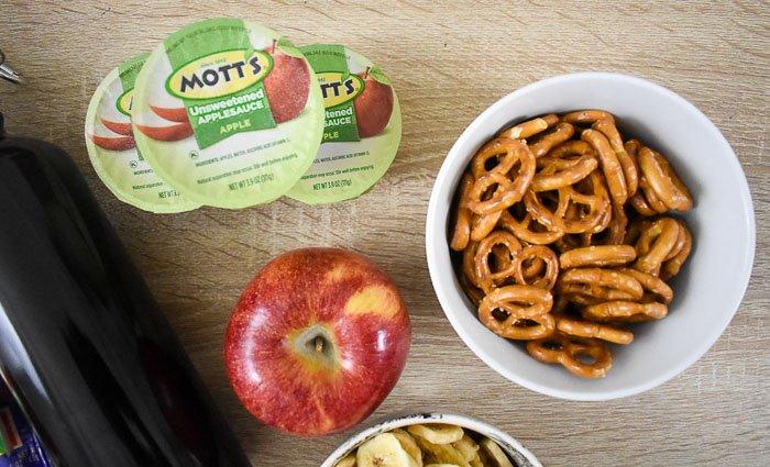 mott's unsweetened applesauce, an apple, and a bowl of pretzels