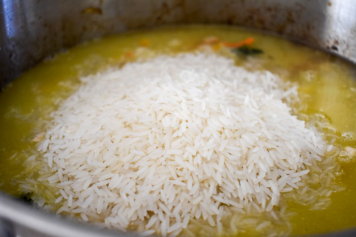 rice in a pot of broth, chicken, and vegetables