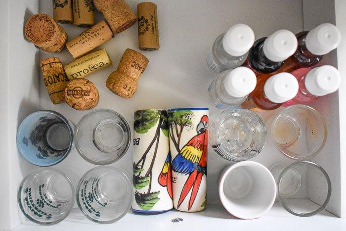 assortment of shot glasses, wine corks, and mini liquor bottles inside a drawer