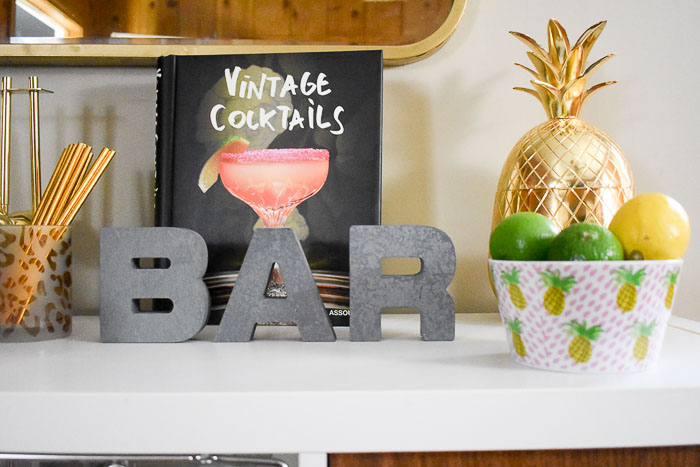 Vintage Cocktails book and other accessories on top of a home bar cabinet