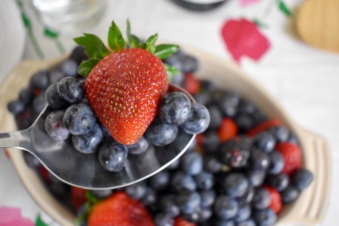 serving spoon of fresh blueberries and strawberries