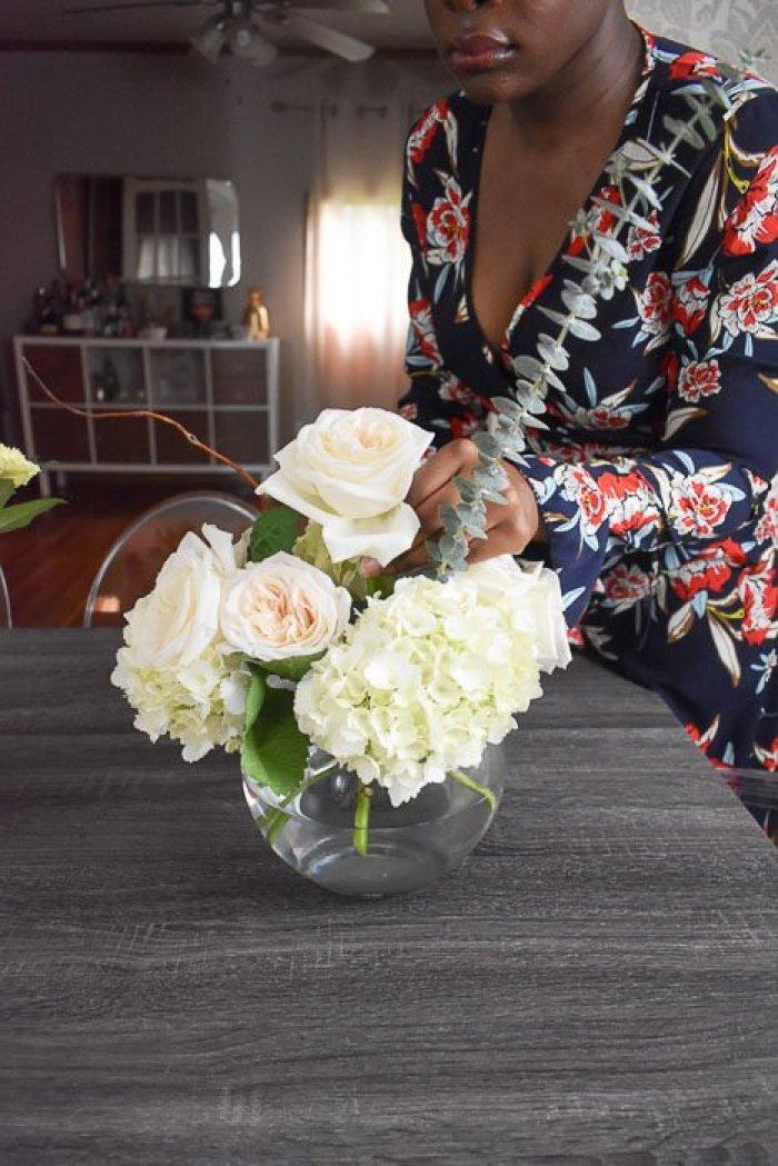 woman arranging garden roses, hydrangeas, and eucalyptus in a globe vase