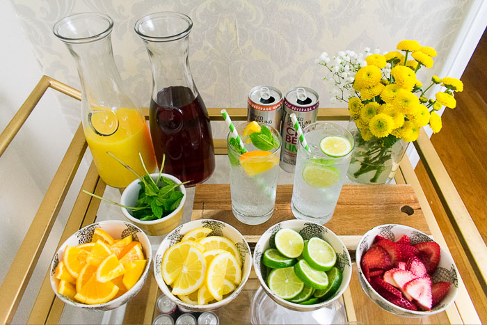 DIY drink station with fresh fruit, mint, fruit juices, and smirnoff spike sparkling seltzer