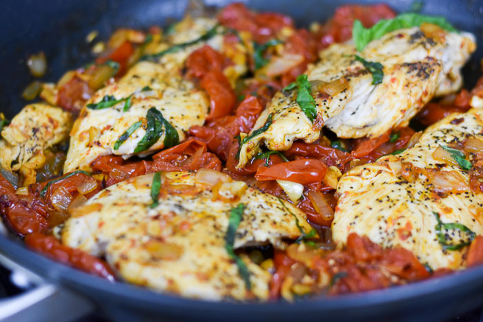 chicken breasts and sauteed tomatoes with basil in pan