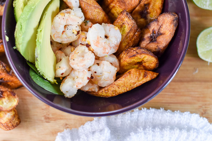 bowl with coconut lime shrimp, fried plantain, sliced avocado, and lime