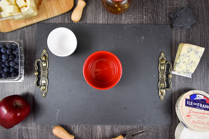 slate cheese board and two ramekins surrounded by cheese board ingredients