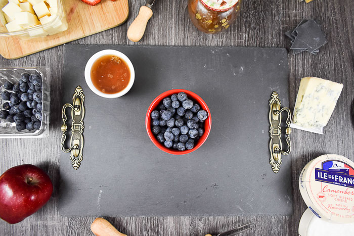 berries and honey on slate cheese board