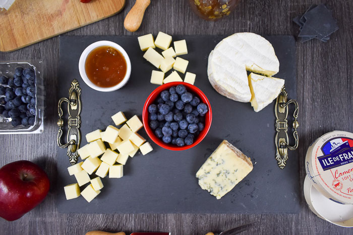 white cheddar, honey, blueberries, camembert, and blue cheese on slate cheese board