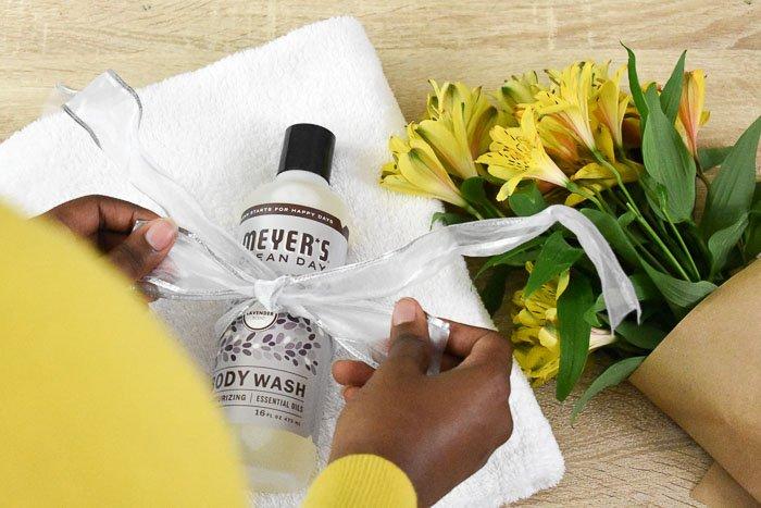 tying ribbon around bottle of Mrs. Meyer's lavender body wash
