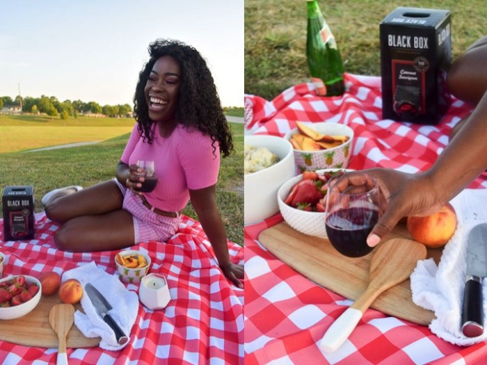 woman in pink holding red wine at outdoor picnic