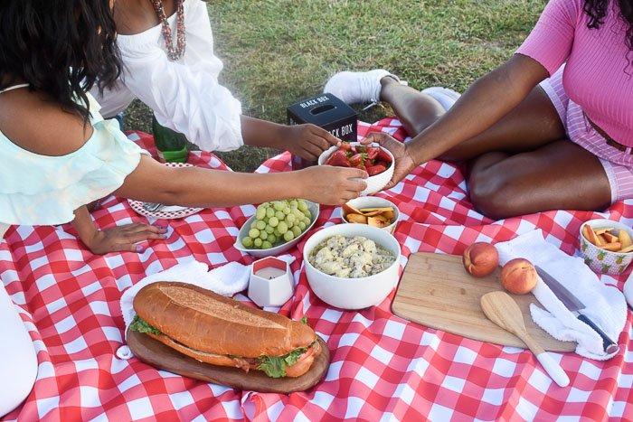 women sharing food at picnic