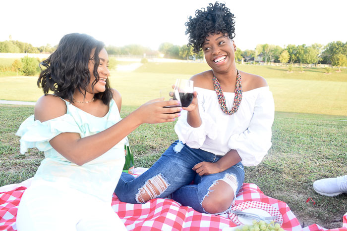 women toasting red wine at picnic