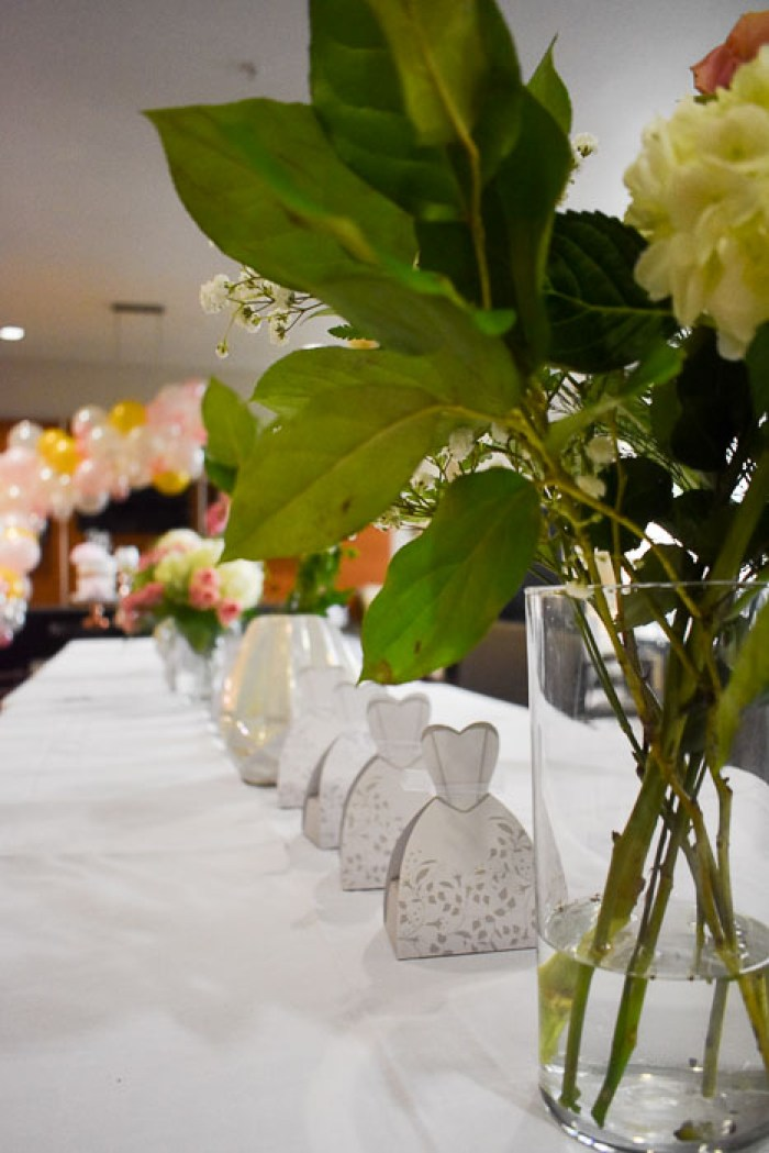 floral arrangement and party favors on table at bridal shower