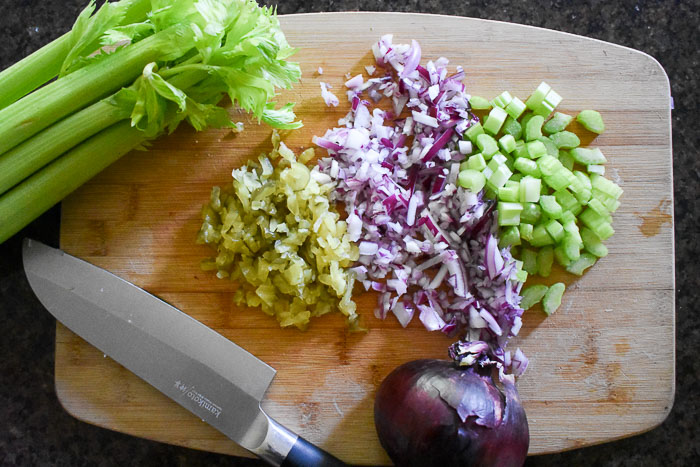 chopped celery, red onion, and pickles on wooden cutting board