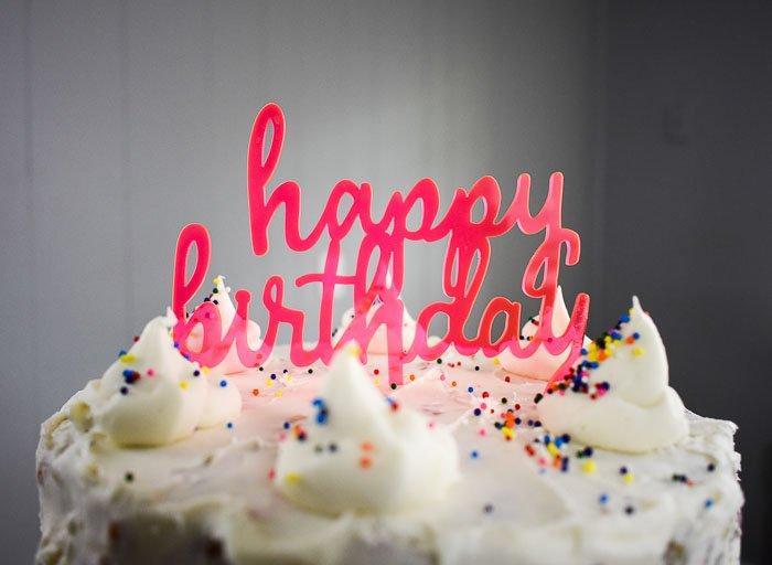 happy birthday topper on bourbon vanilla birthday cake