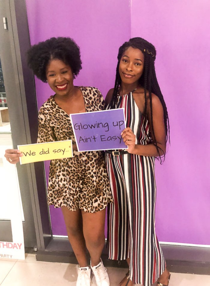 two sisters holding insecure quote signs.