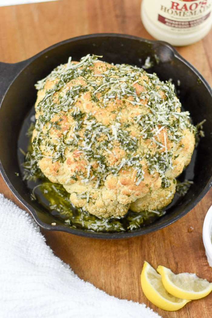 roasted head of cauliflower covered in herbs, olive oil, and parmesan cheese