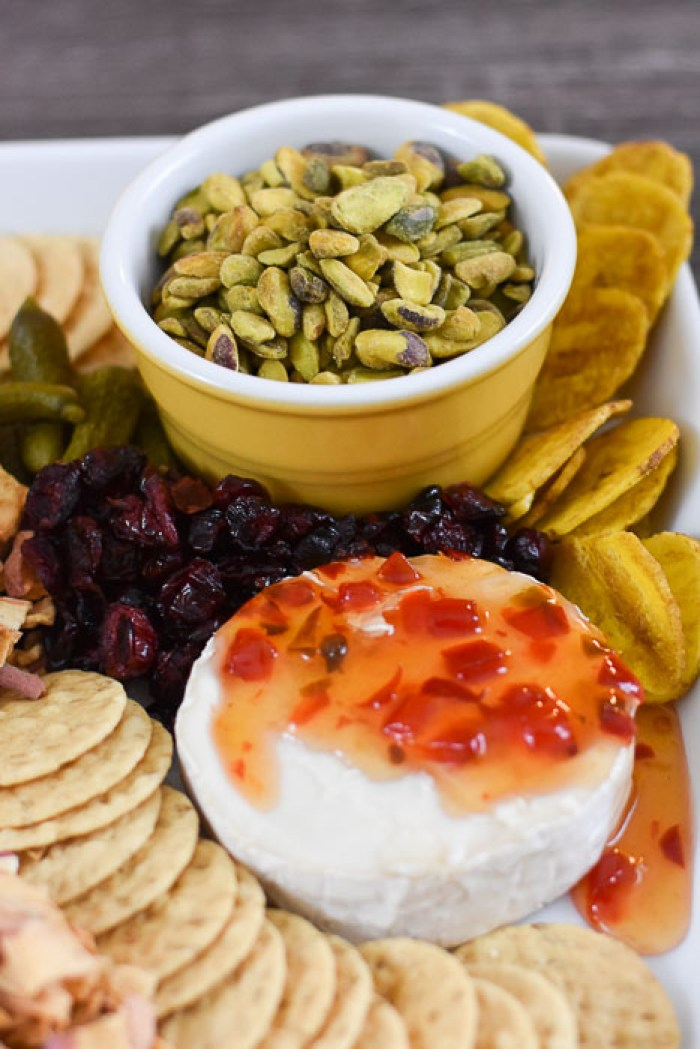 brie cheese, pistachios, plantain chips, dried cranberries, cornichons, and crackers on cheese tray