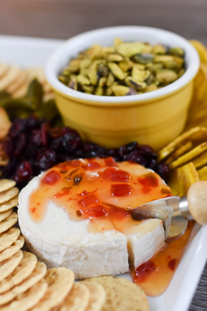 wheel of goat milk brie cheese topped with Trader Joe's pepper jelly