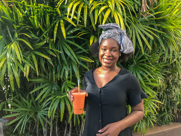 Dash of Jazz holding sunrise smoothie at Tucker & Bevvy's Waikiki Beach