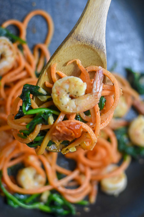 cooked shrimp and veggies on wooden spoon