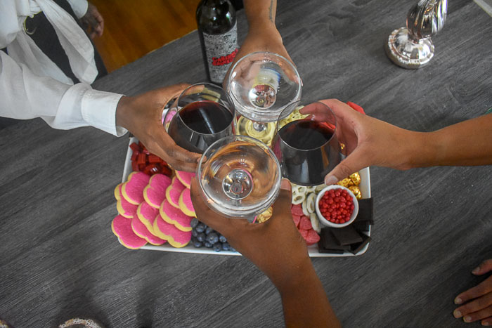 toasting sparkling water and red wine over dessert board