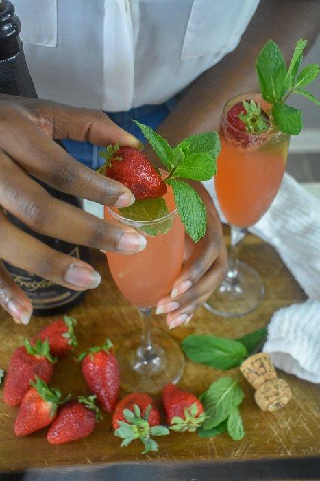 adding fresh strawberry to strawberry mint mimosa