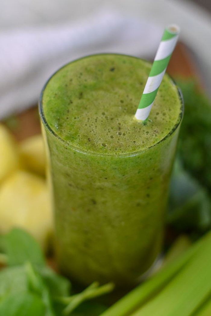 glowing skin green smoothie in glass with striped paper straw