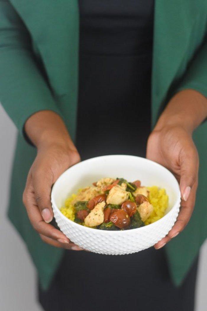 holding lemon garlic chicken & veggie rice bowl