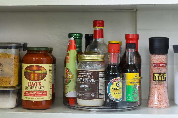 sauces and oils organized in lazy Susan on pantry shelf
