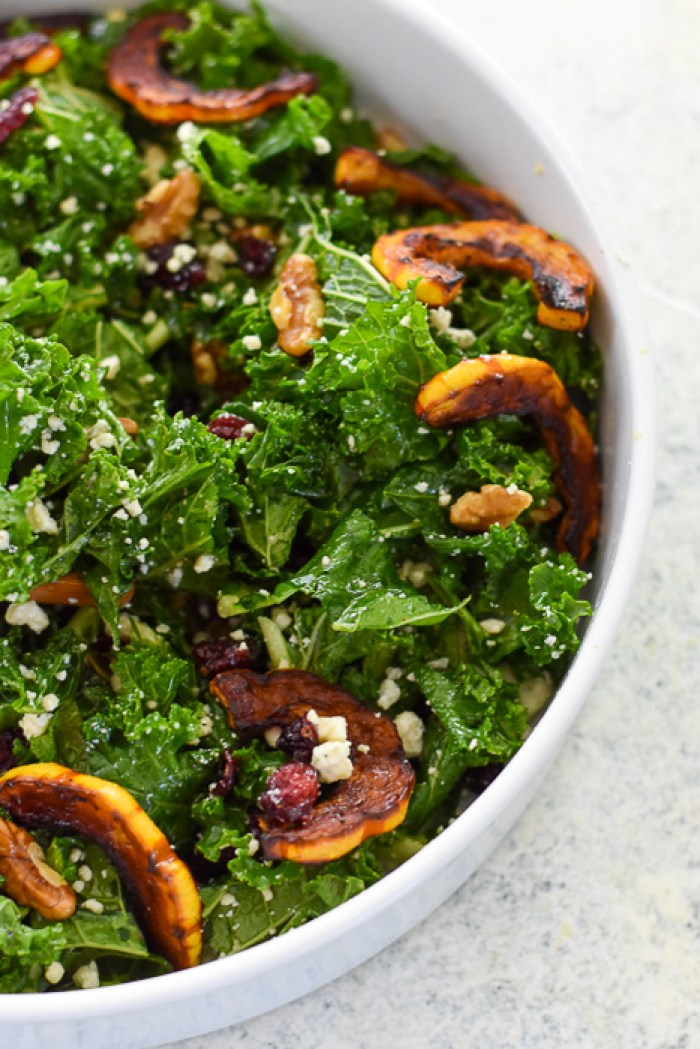 autumn chopped kale salad with slices of roasted delicata squash