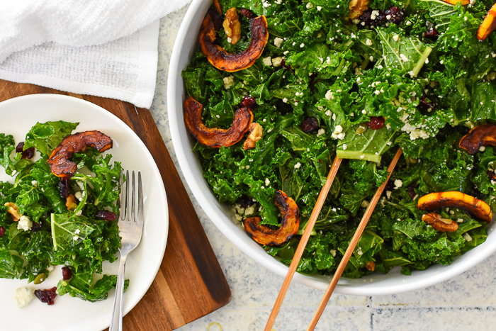 massaged kale salad topped with gorgonzola cheese and delicata squash in serving bowl.