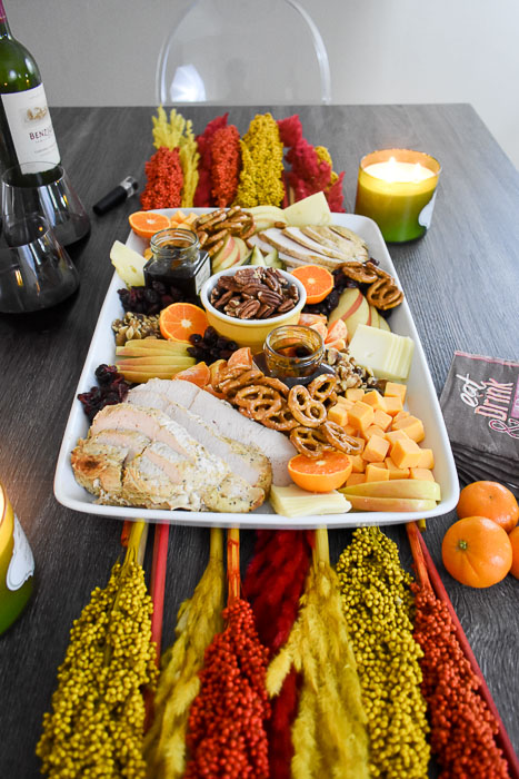 Thanksgiving snack board on table with candle