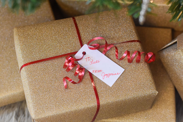 presents wrapped in gold glitter paper under Christmas tree