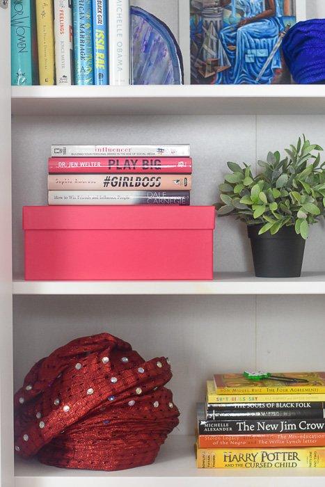 Nigerian gele, books, and succulent plant styled on IKEA Hemnes bookshelf