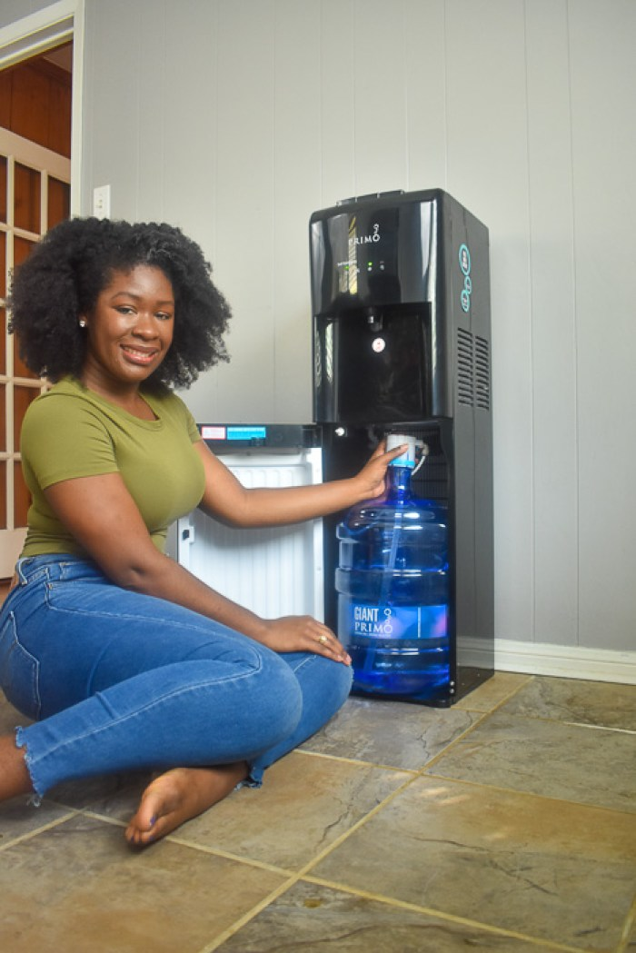 Dash of Jazz setting up Primo Water dispenser in kitchen