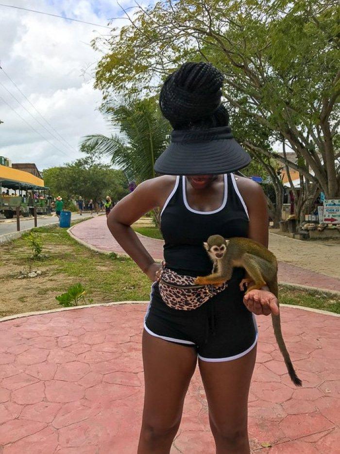 holding small monkey outside Tulum Mayan Ruins