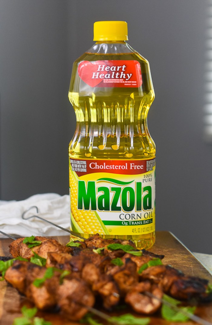 bottle of Mazola corn oil next to grilled chicken skewers