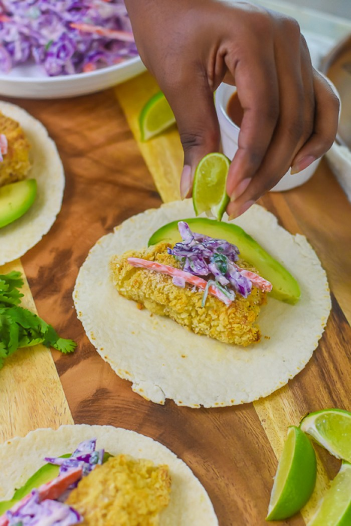 squeezing fresh lime over fish taco