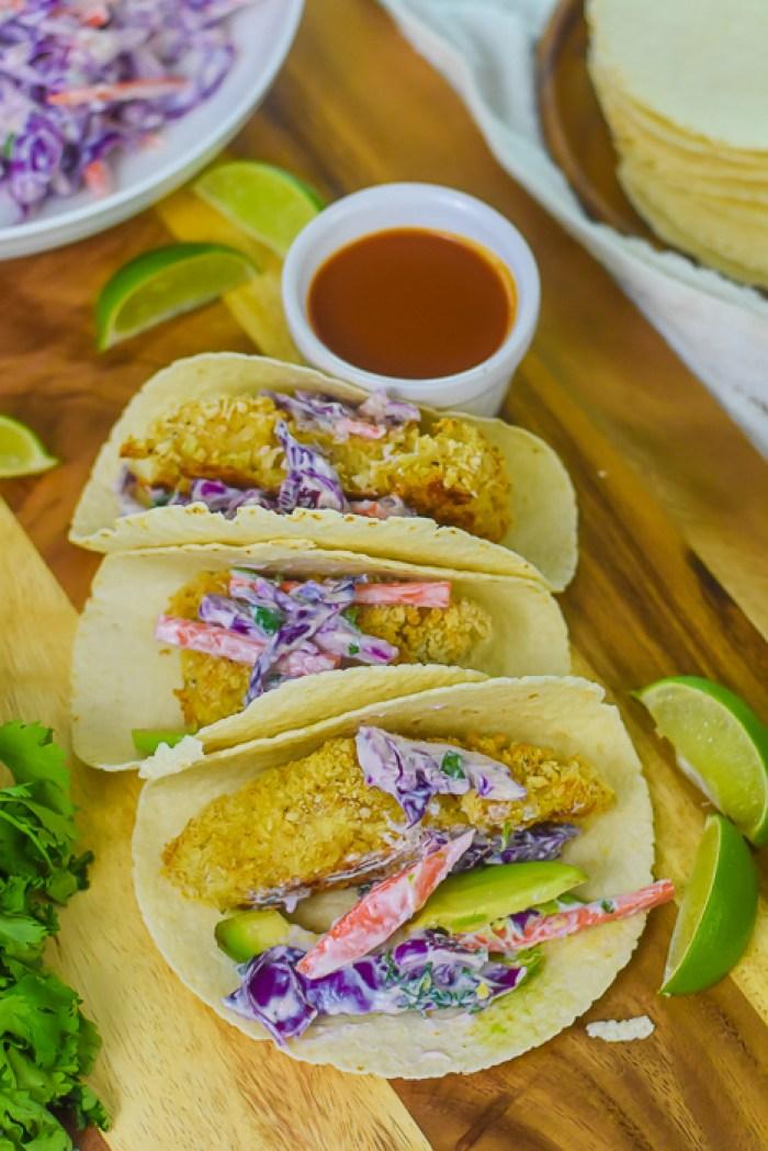 three fish tacos and garnishes on cutting board