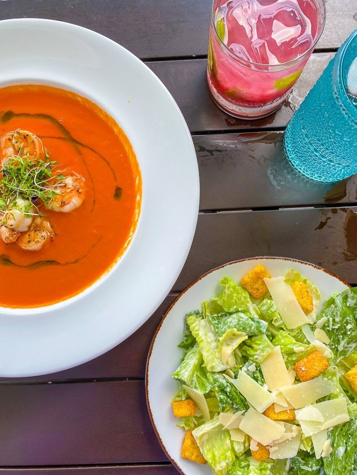 bowl of tomato soup, cocktail, and Caesar salad on table