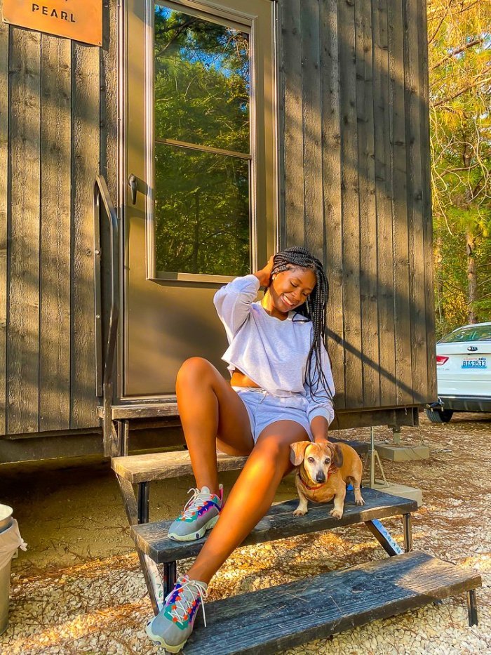 Jazzmine sitting on Getaway Houston cabin porch with dog, JoJo